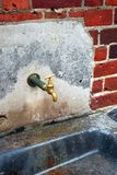 Brassy tap. An old brass outdoor tap mounted on the  brick wall Royalty Free Stock Photos