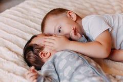 Brat i jego rozochocony małej siostry lying on the beach na łóżkowej dziewczynie ziewamy fotografia stock