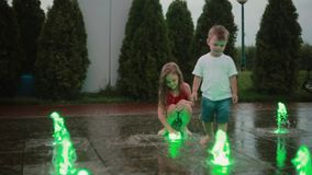 Brat i siostra bawić się przy barwioną fontanną wpólnie Chłopiec i dziewczyna dotyka wodnego strumienia, mokrzy dzieci w gorącym  zdjęcie wideo