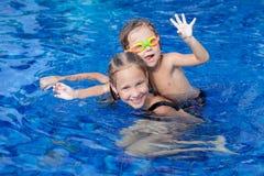 Brat i siostra bawić się w pływackim basenie Fotografia Royalty Free