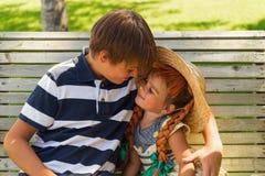 Brat i siostra bawić się wpólnie siedzieć na ławce outdoors Zdjęcia Royalty Free