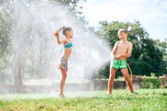 Brat i siostra bawić się wraz z podlewanie wężem elastycznym w ogródzie obraz stock