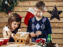 Brat i siostra dekoruje piernikowego dom obraz stock