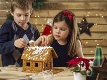 Brat i siostra dekoruje piernikowego dom obraz royalty free