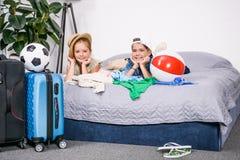 brat i siostra kłaść na łóżku z walizek iść obraz stock