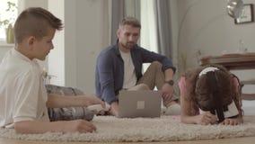 Brat i siostra kłaść na podłodze na puszystym dywanie używać rzeczywistość wirtualna szkła, ojca obsiadanie na zbiory wideo