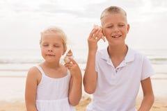 Brat i siostra trzyma seashell Fotografia Stock