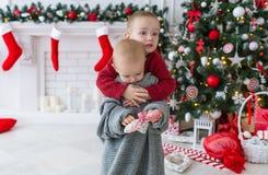 Brat obejmuje małej siostry w święto bożęgo narodzenia Zdjęcia Royalty Free