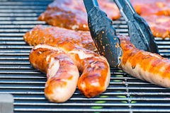 Brat sausage is served on the charcoal grill with the grill tongs Stock Photo