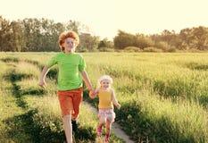 Brata i siostry bieg na polu Obrazy Royalty Free