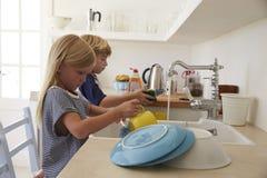 Brata i siostry klęczenie na krzesłach myć up w kuchni Obrazy Royalty Free