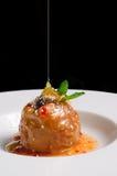 Bratapfel mit Honigkaramel auf weißer keramischer Platte auf schwarzem Hintergrund Stockfotos