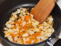 Braten der Karotten und der Zwiebeln. Lizenzfreies Stockfoto