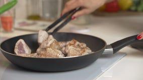 Braten des Fleisches in der Bratpfanne auf dem elektrischen Ofen Frau mischt gebratenes Fleisch in der Bratpfanne auf dem elektri stock video