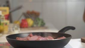 Braten des Fleisches in der Bratpfanne auf dem elektrischen Ofen Frau mischt gebratenes Fleisch in der Bratpfanne auf dem elektri stock video footage