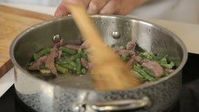 Braten des gehackten Rindfleisches mit grünen Bohnen, Knoblauch und Kräutern in einer Stahlwanne stock video footage