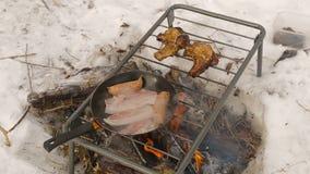 Braten des Speckes und der Steaks auf einem Feuer im Winter im Schnee Nahaufnahme stock video