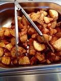 Braten-Kartoffeln in einem Metallumhüllungs-Behälter mit den Zungen Stockbild