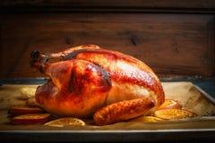 Braten Sie ganzen Truthahn oder Huhn über hölzernem Hintergrund