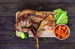 Braten Sie ganzes Kaninchen auf einem hölzernen Brett mit gebackenen Karotten und Rosenkohl auf einem dunklen Hintergrund eine fe Lizenzfreie Stockfotos