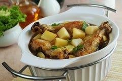 Braten von einer Kartoffel und von einem gebratenen Huhn Stockfotos