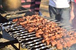 Bratenfleisch auf Aufsteckspindeln auf offenem Feuer Stockfotos