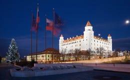 Bratislava - castello dal Parlamento alla notte ed albero di Natale e bandiere Immagini Stock