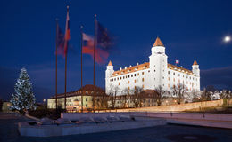 Bratislava - castelo do parlamento na noite e a árvore e as bandeiras de Natal Imagens de Stock
