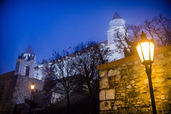 Bratislava castle by night. A lamp shines on the walkway up to the massive construction overlooking the capital of the Slovak Republic Royalty Free Stock Photos