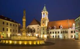 Bratislava - huvudsaklig fyrkant i aftonskymning med stadshuset och jesuitkyrkan. arkivbilder