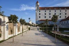 Bratislava slott från den trädgårds- gränden på solnedgången Royaltyfri Foto