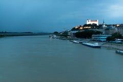 Bratislava slott ovanför Danube River på skymning Arkivbilder