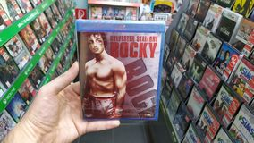 Man holding Rocky movie on blu-ray disc in store in store. Bratislava, Slovakia, april 25, 2019: Man holding Rocky movie on blu-ray disc in store in store royalty free stock image