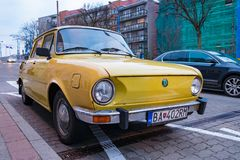 Classic vintage car yellow Skoda parked in city. stock images