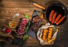 Bratpfanne, Minze, Mais, Grill, Würste auf Holztisch lizenzfreie stockfotografie