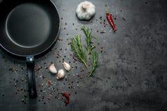 Bratpfanne mit Knoblauch und Pfeffer auf schwarzem Hintergrund lizenzfreie stockfotos
