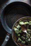 Bratpfanne und eine Platte des gefrorenen Spinats auf Schiefer Lizenzfreie Stockfotografie