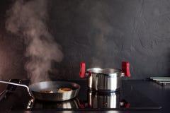 Bratpfanne und Kochentopf auf Induktionskochfeld, Dampf steigt Schwarze strukturierte Küche lizenzfreie stockbilder