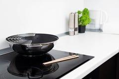 Bratpfanne und Steuerknüppel in der modernen Küche lizenzfreie stockfotografie