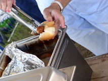 Brats served up. Vendor places brat on bun at public event. Popular at ball games, beer & brats are a must stock photos