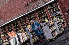 Brattle Book 3. Outdoor bookstore with female shopper reviewing books on bottom shelf during New England winter. 2-25-13 Brattle Book Shop-- 9 West St. Boston Stock Photos