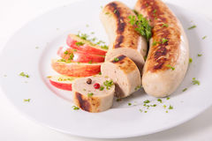 Bratwurst and apple Stock Images