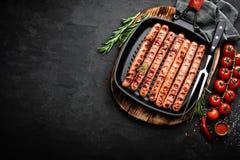 Bratwurst arrostito delle salsiccie in padella della griglia su fondo nero Vista superiore Cucina tedesca tradizionale fotografia stock libera da diritti