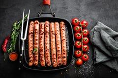 Bratwurst asado a la parrilla de las salchichas en sartén de la parrilla en fondo negro Visión superior Cocina alemana tradiciona fotografía de archivo libre de regalías