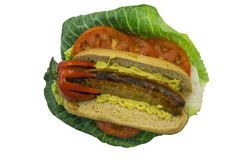 Bratwurst on Bun with Mustard and Garnish. Isolated cooked bratwurst sausage on bun with mustard, tomatoes, lettuce, cabbage leaf, red pepper cap Stock Photo