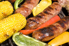 Bratwurst and corn cob on barbecue Royalty Free Stock Images