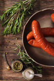 Bratwurst grill with salt and pepper rosemary. Bratwurst grill with salt and pepper and rosemary on brown wooden background stock photography