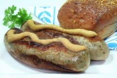 Bratwurst with mustard and bread. Bratwurst with mustard and dark bread stock photos