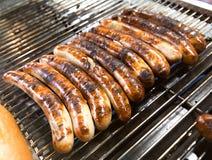 Bratwurst que son asados a la parrilla en una parrilla al aire libre del Bbq Imagen de archivo libre de regalías