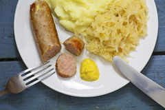 Bratwurst with sauerkraut, mashed potatoes and mustard on a rust Stock Image